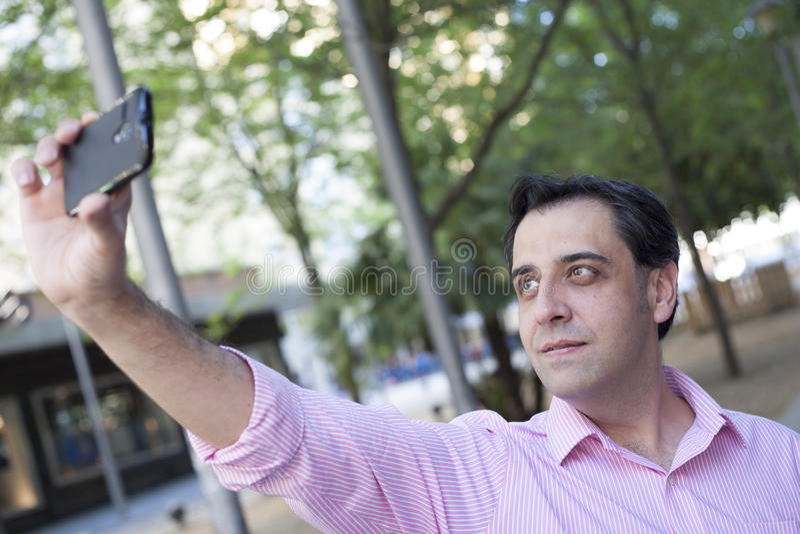 Man som tar självståenden med mobiltelefonen arkivfoton