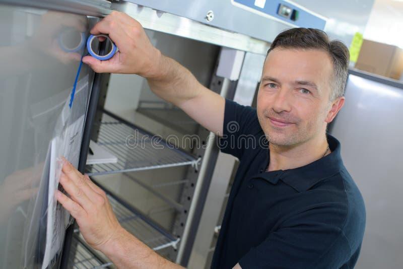 Man som tejpar anvisningar till dörrkylskåpet fotografering för bildbyråer