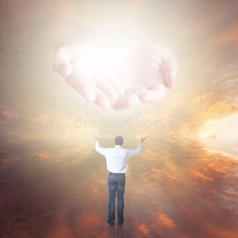 Man som tillber guden Händer med ljust komma från himlen arkivfoto