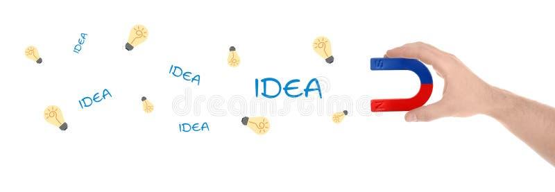 Man som tilldrar idéer i formen av ljusa kulor med magneten på vit bakgrund id?rik design royaltyfria bilder