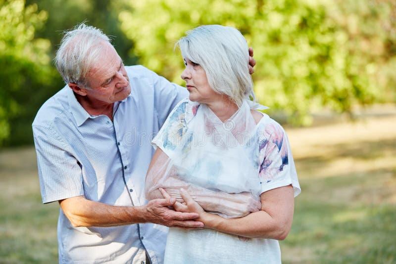 Man som tröstar den gamla kvinnan med den brutna armen arkivfoto