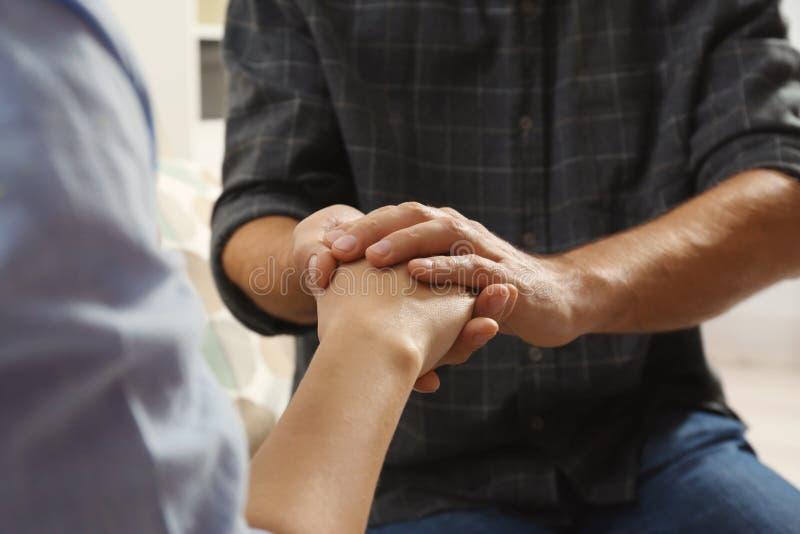 Man som tröstar kvinnan, closeup av händer arkivfoto