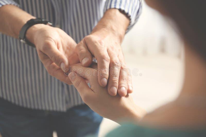 Man som tröstar kvinnan på ljus bakgrund, closeup av händer royaltyfria foton
