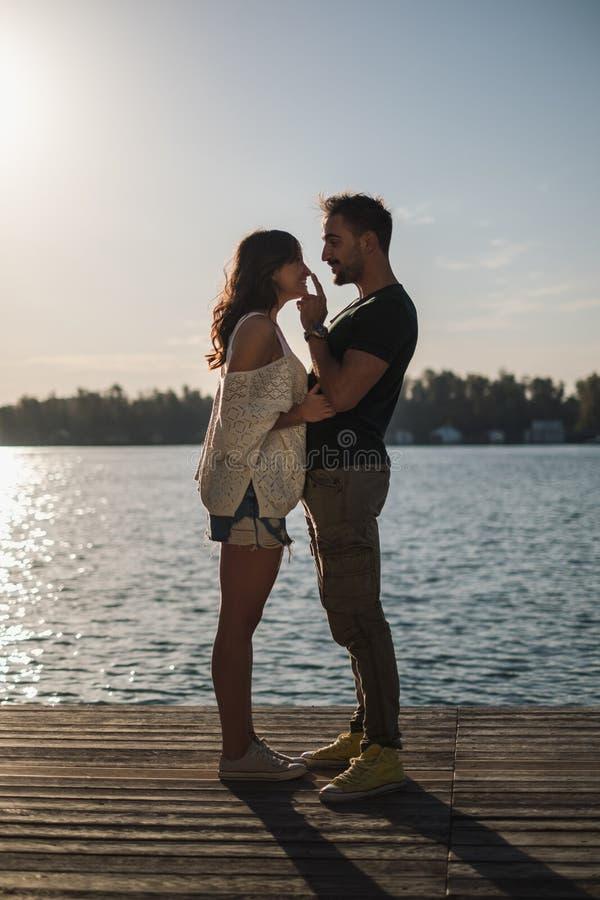 Man som trycker på hans le flickvännäsa vid floden royaltyfri bild