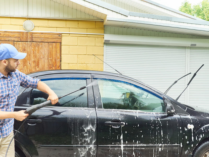 Man som tvättar hans near hus för svart bil arkivfoto