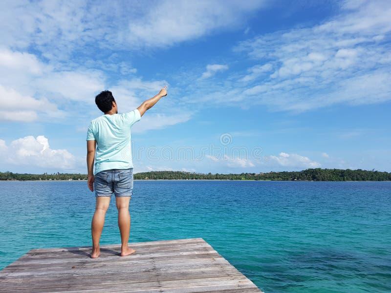 man som tycker om havslandskap, medan stå på strandträpir med den lyftta handen mot himmelbakgrund med kopieringsutrymmeområde fö arkivbilder