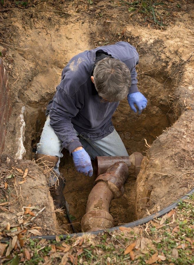 Man som undersöker gamla Clay Ceramic Pipe Sewer Line i hål i jordning royaltyfria bilder