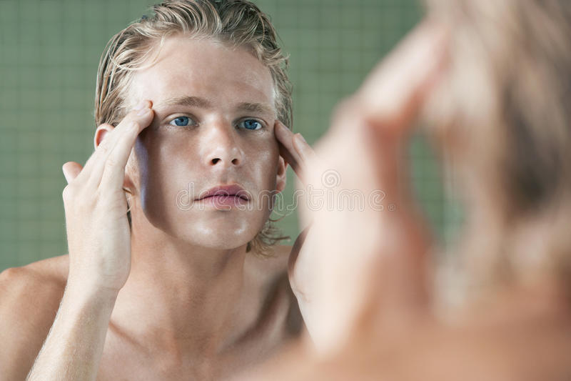 Man som undersöker sig i Front Of Mirror arkivfoto