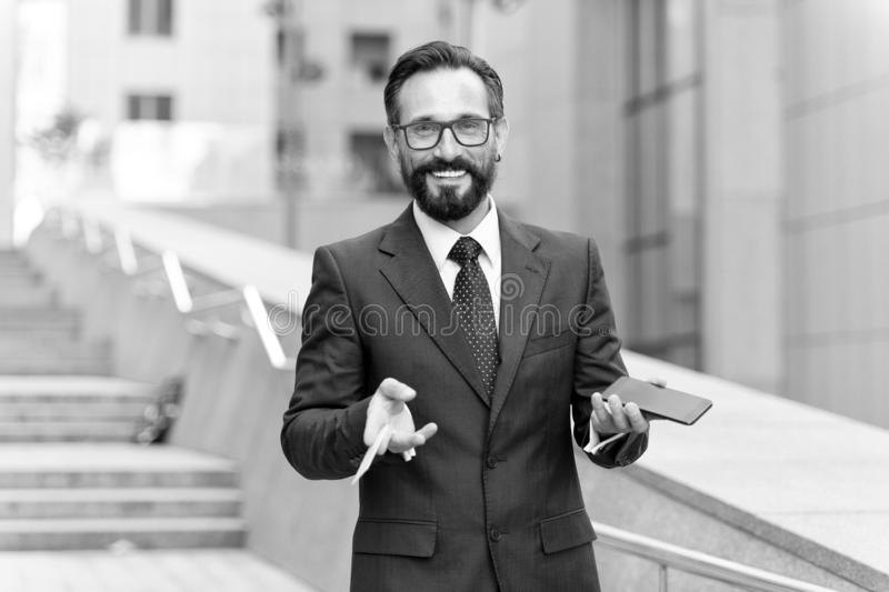 Man som upp rymmer kreditkorten och gör online-betalning på hans mobiltelefon med byggnadsbakgrund lyckligt affärsmananseende på  arkivfoto