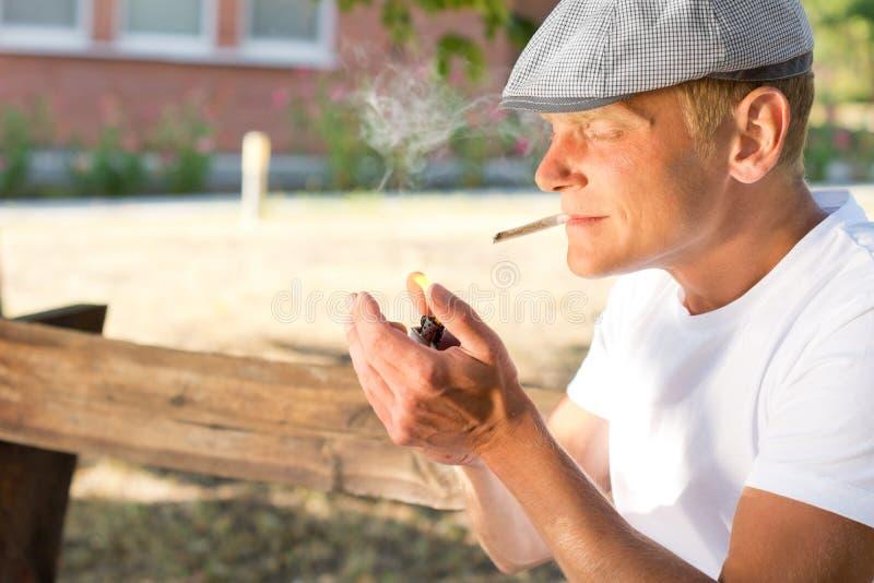 Man som upp tänder en cannabisskarv arkivfoton