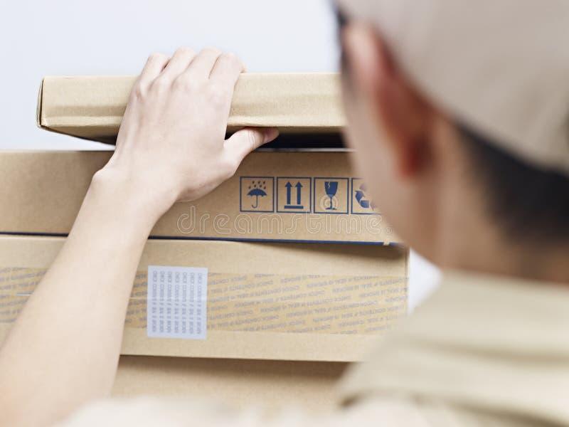 Man som upp väljer en lådapacke arkivbild