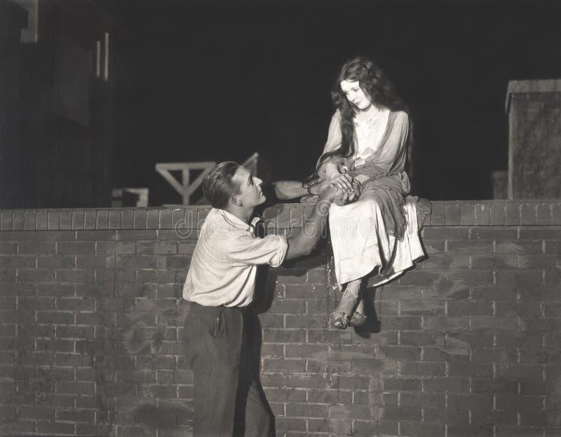 Man som uppvaktar kvinnasammanträde på tegelstenväggen royaltyfri fotografi