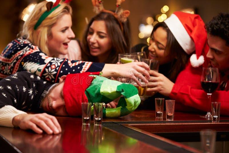 Man som ut passeras på stång under juldrinkar med vänner arkivfoto