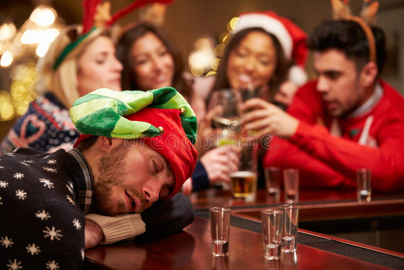 Man som ut passeras på stång under juldrinkar med vänner fotografering för bildbyråer