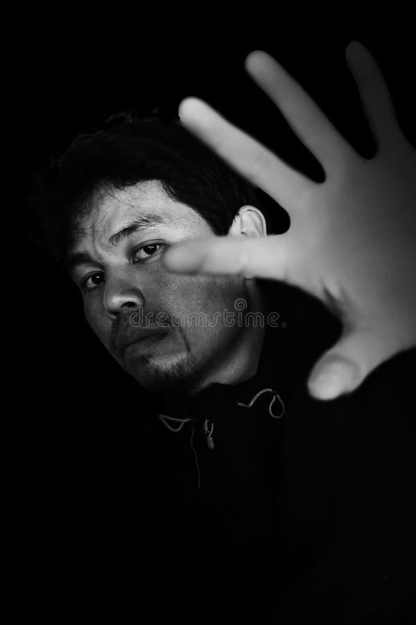 man som ut sträcker handen för att öppna något med skräck arkivfoto