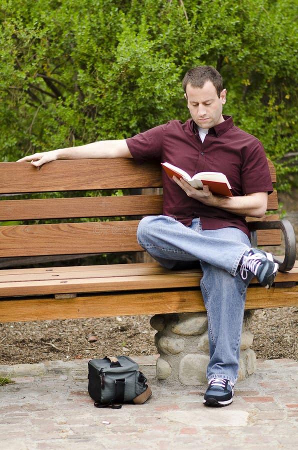 Man som utanför läser en bok royaltyfria bilder