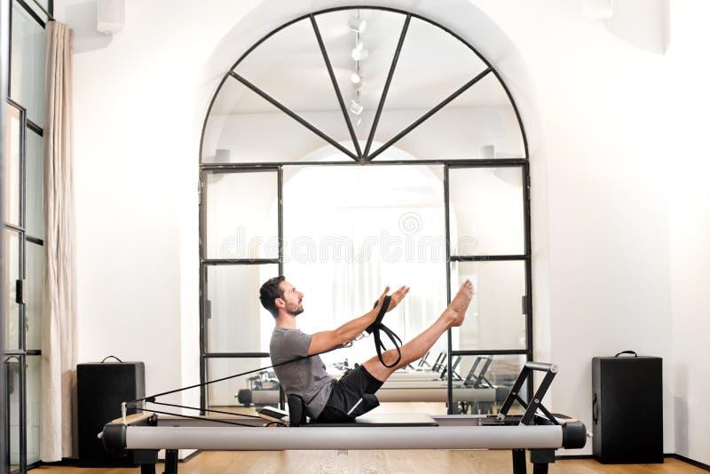 Man som utför pilateskuggfrågaövning i en idrottshall arkivbild