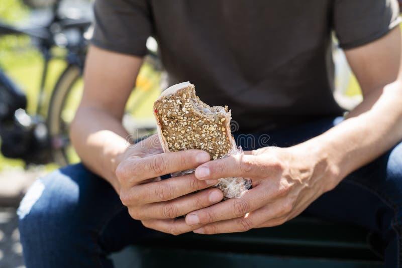 Man som utomhus äter en kalkonsmörgås royaltyfri fotografi