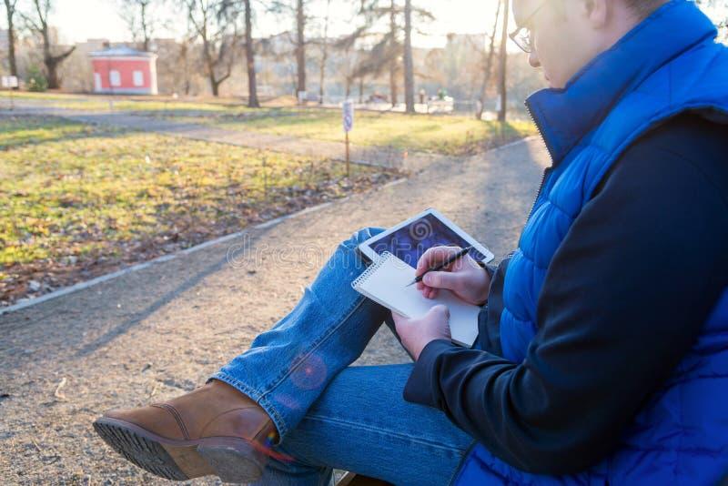 Man som utomhus använder anteckningsbok- och minnestavladatoren fotografering för bildbyråer