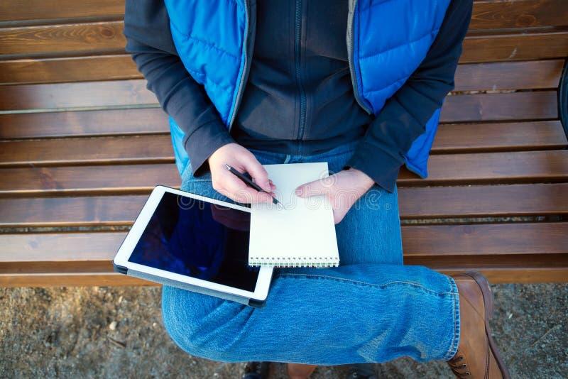 Man som utomhus använder anteckningsbok- och minnestavladatoren arkivfoto