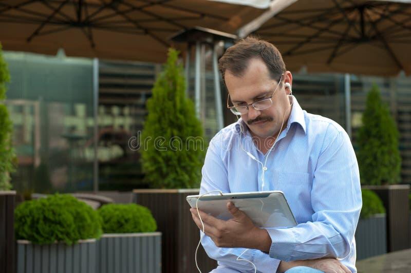 Man som utomhus använder minnestavladatoren arkivbild