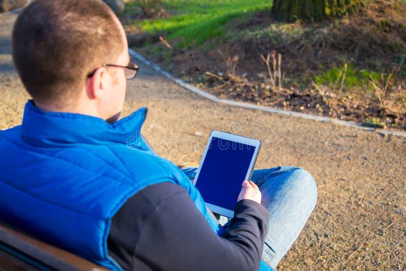 Man som utomhus använder minnestavladatoren arkivbilder