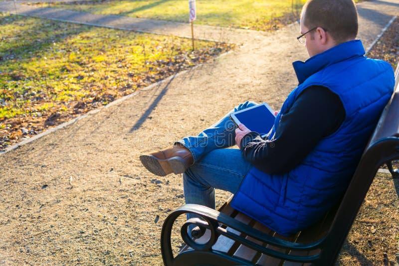 Man som utomhus använder minnestavladatoren royaltyfri fotografi