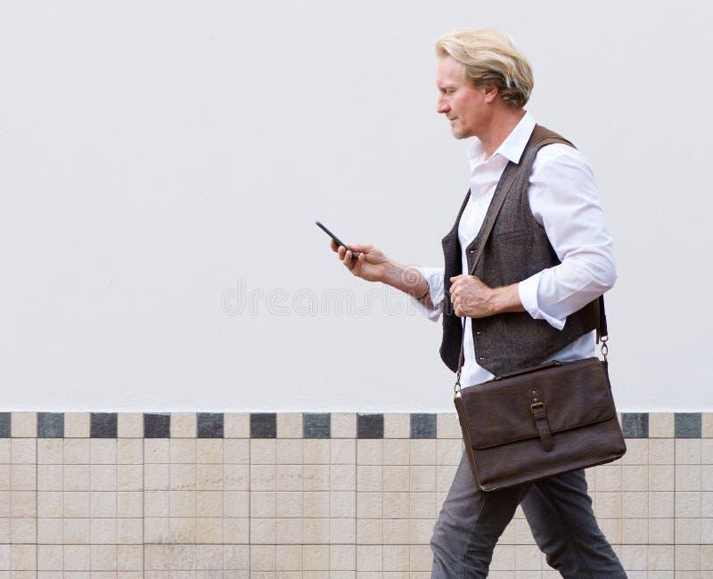 Man som utomhus går och ser mobiltelefonen royaltyfri bild
