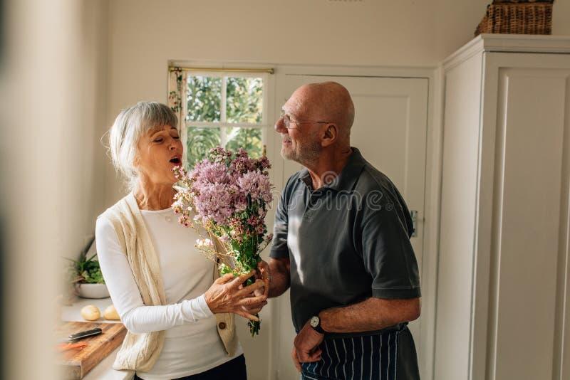 Man som uttrycker hans förälskelse för hans fru som hemma ger henne en grupp av blommor Hög kvinna som är lycklig att se hennes m royaltyfri bild