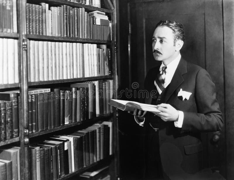 Man som väljer böcker från bokhyllan i ett arkiv (alla visade personer inte är längre uppehälle, och inget gods finns Leverantörw royaltyfri fotografi