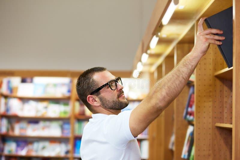 Man som väljer en bok i ett arkiv royaltyfri bild