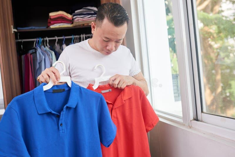 Man som väljer en skjorta för honom arkivbild