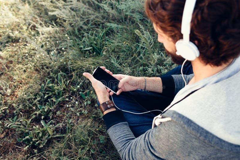 Man som väljer musik på den utomhus- smartphonen arkivfoto