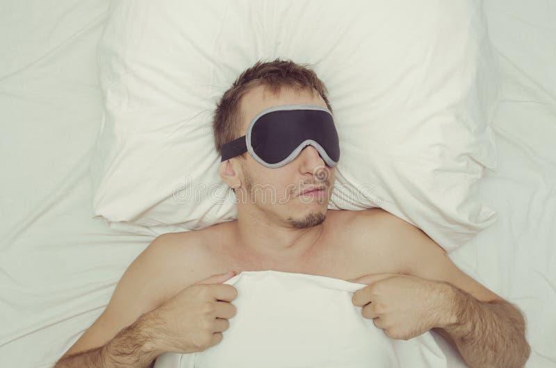 Man som vilar i en maskering för sömn Skäggstubb på hans framsida tröttad man royaltyfri foto