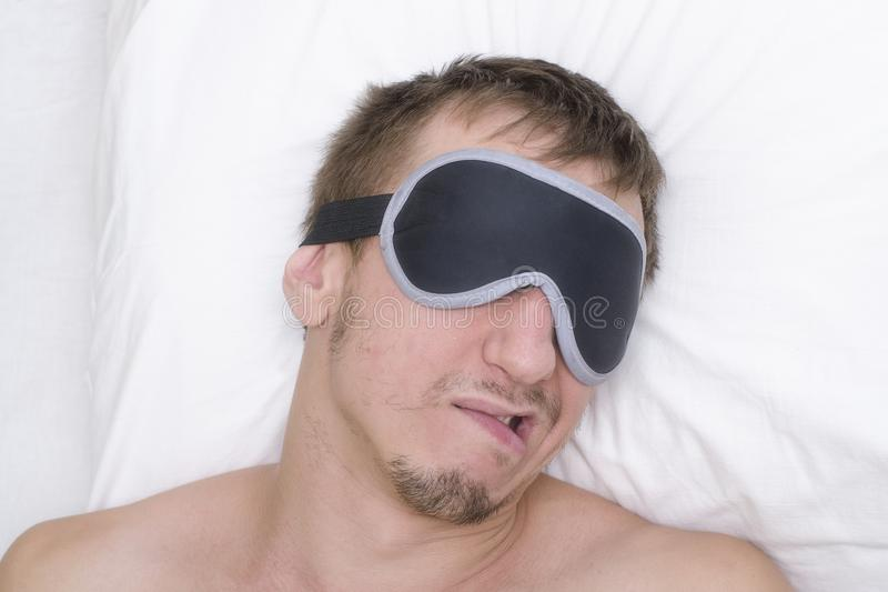 Man som vilar i en maskering för sömn Skäggstubb på hans framsida tröttad man arkivbild