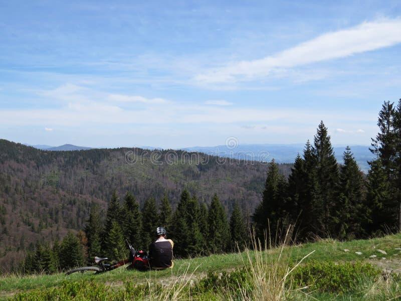 Man som vilar med en cykel och tycker om sikt på berg arkivfoto