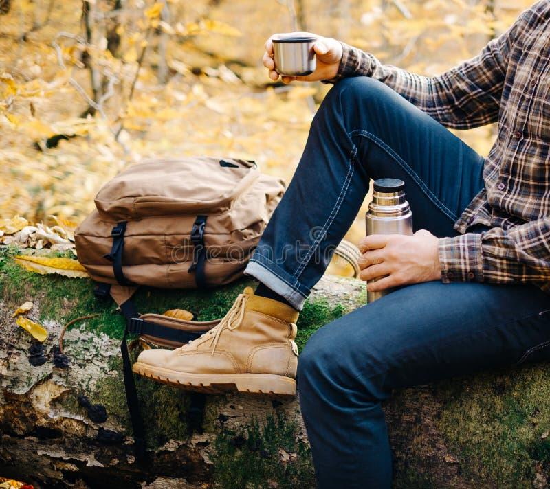 Man som vilar på den stupade trädstammen med termoset fotografering för bildbyråer