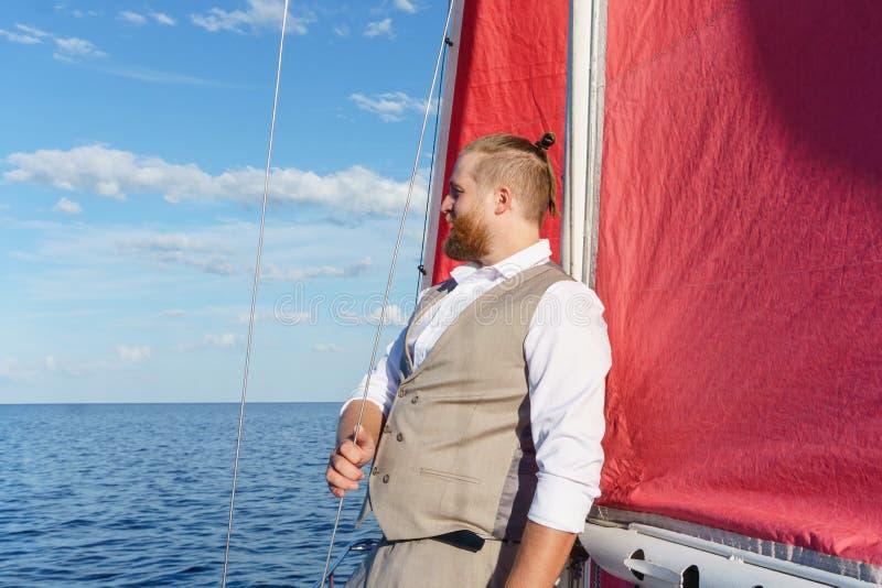 Man som vilar på en segelbåt royaltyfria foton