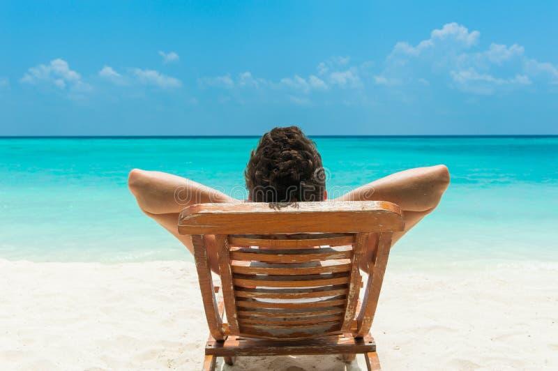 Man som vilar på strand arkivfoton