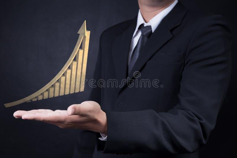 Man som visar den guld- löneförhöjningpilen med grafen arkivbild