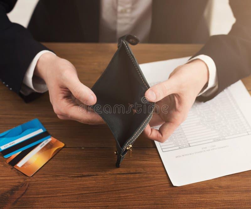 Man som visar den tomma plånboken utan kassa royaltyfri fotografi