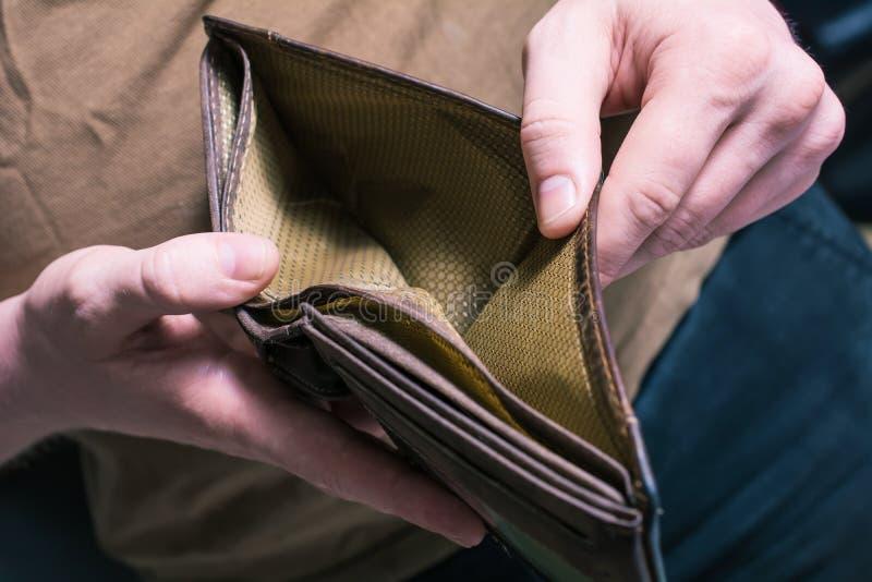 Man som visar hans tomma plånbok - inga pengar lämnade begrepp royaltyfria bilder