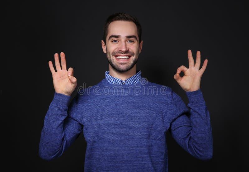 Man som visar reko gest i teckenspråk på svart royaltyfri bild