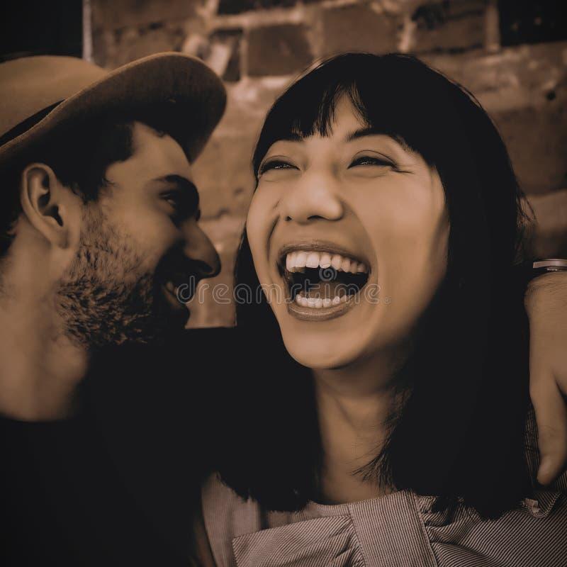 Man som viskar i lyckligt kvinnaöra på kafét royaltyfri foto