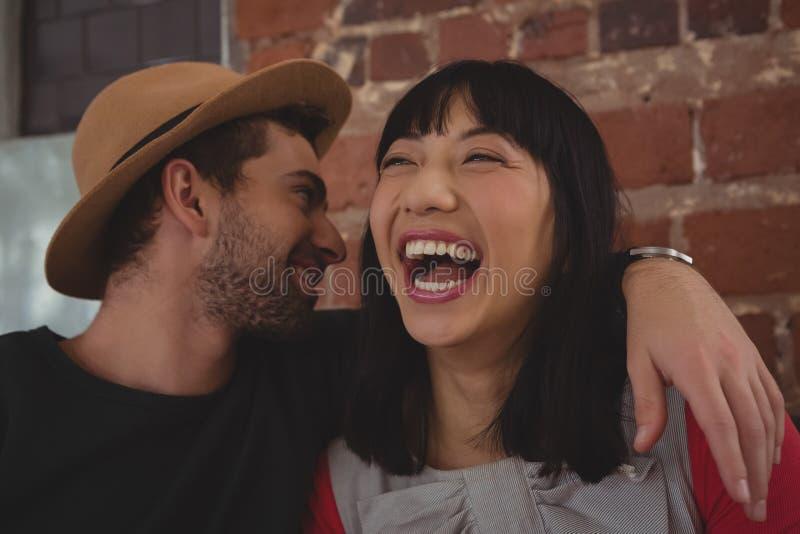 Man som viskar i lyckligt kvinnaöra på kafét royaltyfria bilder