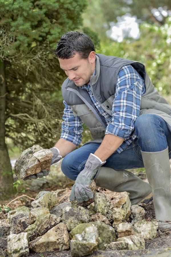 Man sorting through pile rocks stock photos