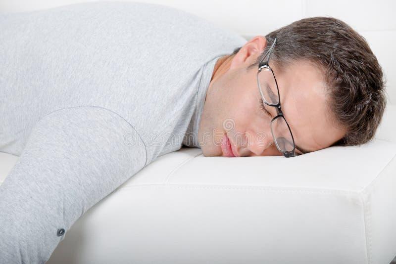 Man sovande på soffaexponeringsglas som skjuts av framsida arkivbild