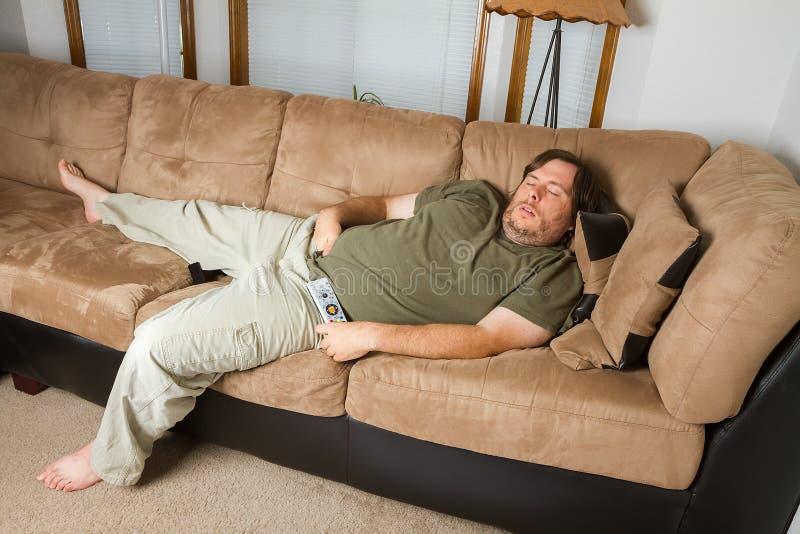 Man sovande på soffan royaltyfri fotografi