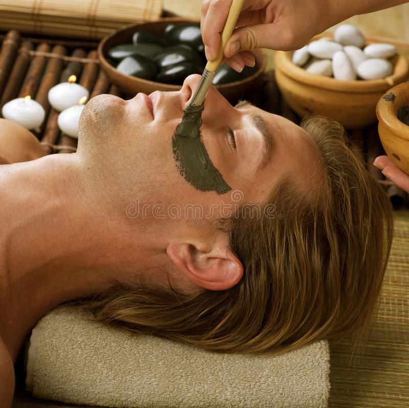 Man in Spa. Spa.Handsome Man with a Mud Mask on his Face royalty free stock image