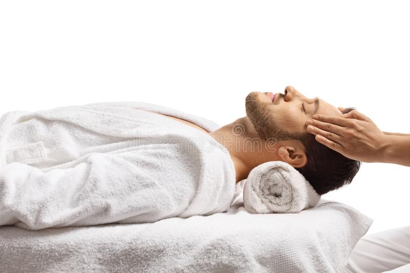 Man at a spa center enjoying a head massage. Isolated on white background royalty free stock photography